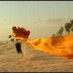 Course avec un chèche et le vent dans le désert tunisien